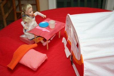 Barbie mange devant sa caravane